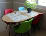 Nouvelles chaises en couleur et table fonctionnelle, ambiance papier peint et peinture dans un camaieu de gris pour les murs